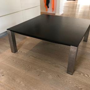 Sofabord fra Kristensen & Kristensen. mål 100x100, højde 40 cm. Sort lakeret eg, med ben i børstet rustfri stål. Der er et lille mærke på bordet, se billedet.