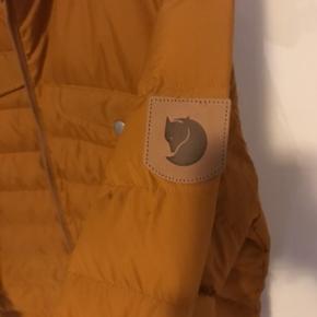 Helt ny ubrugt Fjällräven jakke med tags.Str.L  Nyprisen: 1799kr  https://www.outdoornu.dk/fjallraven-greenland-down-liner-jacket-men.html?gclid=EAIaIQobChMI_OfCwpH85wIVhM13Ch082g45EAQYCCABEgL_tvD_BwE  Fjällräven Greenland Down Liner Jacket Men - Let, varm Herre Dunjakke er perfekt til forår/efterår eller under en Greenland Jacket i koldt vejr. Fremstillet i genanvendt polyester og er foret med etisk producerede dun. Klassiske detaljer såsom bryst lommer med flapper. Praktisk som en isolerende foring og ligeså nyttige som en let jakke i mildere temperaturer.  Familie: Greenland Vægt: 530 g  Ydermateriale: 100% polyester Foring:100% polyester Fyld:80% gåsedun, 20% fjer 600 CUIN Fyldvægt: 140 gr Fluorcarbonfri imprægnering Genanvendt polyester