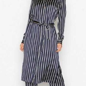 Smuk og elegant skjorte-kjole i blåt satin med hvide striber. Kjolen har en almindelig krave, skjult knapgang, slids forneden og manchet i ærmet. Det fine bindebånd i taljen giver et feminint udtryk til kjolen.  Krøller ikke  100% Polyester  Ekstra skånevask ved 30 grader
