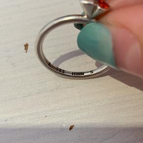 Smuk ring med to hjerter. Det ene er sølv, den anden er rød. Går rigtig godt sammen med andre ringe Størrelsen er s/50