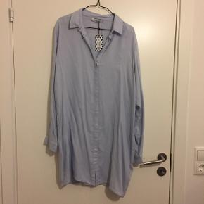 Super sød lang skjorte i lys blå fra Pieces. Aldrig brugt og stadig med prismærke. Str m   Afhentes i Vestamager eller eller sendes på købers regning. :-) Np 229kr Farve: lys blå