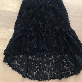 Fin transparent nederdel i en slags blonde mønster. Nederdelen er forret og er længere bagtil. Aldrig brugt. Den er fra ZARA og er lidt lille i størrelsen.  Den måler 35 cm i taljen (svt en talje på ca 70 cm). Længden bagtil er 76 cm og fortil 55 cm.  Kvittering haves.