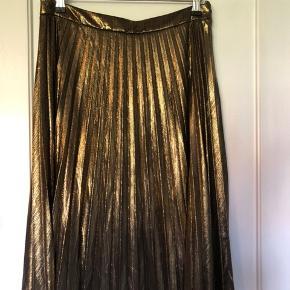 Fejl køb Guld metallic nederdel fra YAYA.  Længde til lige under knæet. Lidt stor i størrelsen. Har sort underskørt så den falder rigtig pænt. Lukkes med lynlås og knap i venstre side.  100% polyester