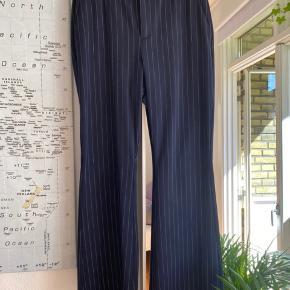 Mørkeblå med striber og brede ben.  Har været brugt få gange.