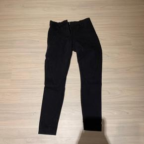Bukserne er brugte og trænger derfor til en omgang med sort farve. Ellers er der ingen tydelige tegn på slid. Bukserne er i størrelse 25 i livet.