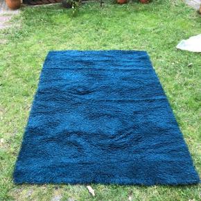 Blåt ryatæppe fra 1960'erne sælges: Ægte dansk Rya tæppe fra Ege tæpper i petroleumsblå uld. Købt i 1960'erne.  Meget fin stand.  Måler 140 x 200 cm.  Afhentes hos mig på indre Nørrebro i København.