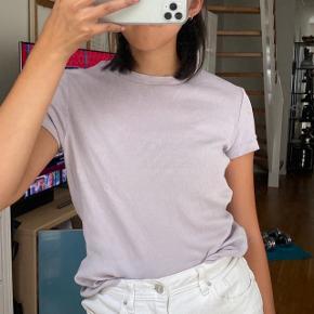 Super sød t shirt fra monki i en pastel lilla /lyselilla farve, farven er som på de første billeder. Det er en str medium men ses her på en small, der er stræk i den så den kan passes af de fleste. To små pletter på den, men det er ikke alt for tydeligt.   Mængderabat gives