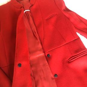 Den skønneste frakke i knald rød farve. Meget feminint figursyet snit. Ikke brugt ret meget. Har taget mærke ud i nakken, men mener det er en str 38/40 :-)