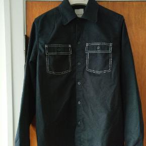 Wood wood skjorte fra AW 163 I rigtig fin condition da den ikke er blevet luftet som fortjent. Lavet i en kraftig kvalitet af polyester og bomuld og kan også benyttes som overskjorte  Mp 375