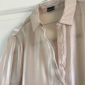 Skjortekjole fra Gina Tricot i skinnende beige stof. Brugt en enkelt gang og fremstår som ny.