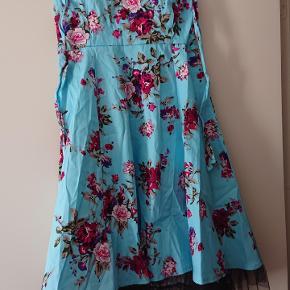 Smuk, lyseblå halterneck kjole med blomster. Str L.  BM: ca 2 x 40 cm. Længde 84 cm. Bånd til at binde i nakken, er hver ca 60 cm.  Lille lynlås i siden af barmen. Og kort kant af sort tyl nederst på kjolen.  #tuesdaysellout