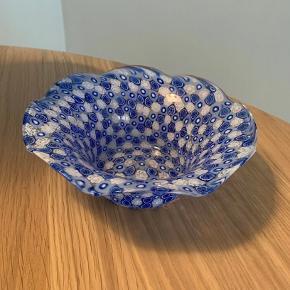 Murano skål med blå og hvide blomster sælges til kr. 375.  Ø: 17 cm., H: 6 cm.  Ingen skår.   Kan afhentes på Østerbro eller sendes mod betaling af porto.