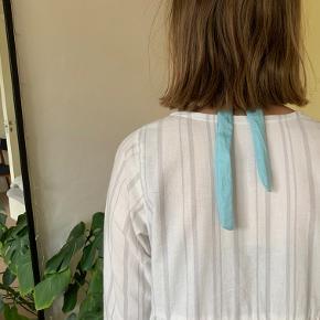 Perlehårbåndet med håndsyede blå perler.  Bindebånd i nakken så hårbåndet passer alle størrelser hoveder. Produceret i genbrugsmaterialer, stoffet er fra et tidligere dynebetræk.  Kan bruges både i løst og opsat hår.