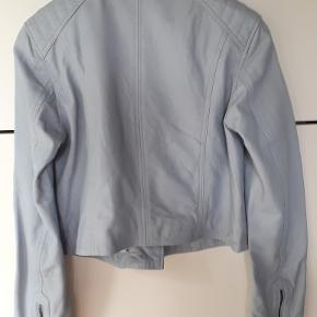 Lyseblå Læderjakke 100% Læder Klassisk Læderjakke i Bikerfacon i en flot lyseblå farve. Jeg vil nærmest kalde den isblå. Jakken er ny og ubrugt.  Materiale: 100% Læder (=glat skind), For 100% Polyester  Jakkens mål: Bryst 100 cm. Omkreds bund 100 cm. Længde 48cm (+ krave 4 cm.) Ærme 64 cm.