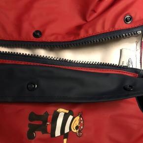 Fin regnfrakke i str. 92. Materiale: PU Tricoat. Med lynlås og trykknapper. Piratlogo på fronten, mørk blå og rød med reflesstriber.