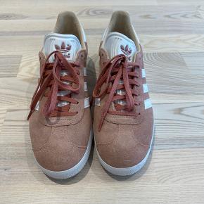 Adidas Originals GAZELLE Sneakers i lys fersken, str. 41  Farven hedder ash pearl  Dame sneakers  Oprindelig pris 799 kr.   Skoene er købt i efteråret 2019 og er brugt 1 gang.  De er så godt som nye.  Bor i Rødovre, arbejder i Bagsværd og kan hentes eller evt. mødes i København og omegn hvis det passer sammen.   Kan sendes på købers regning.