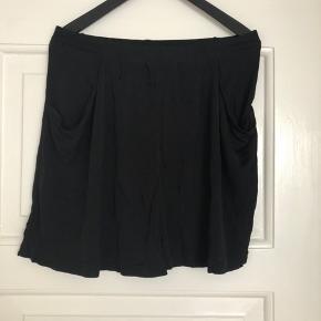 Designers Remix shorts der falder, så de ses som en nederdel.  Lommer ved siderne foran. Elastik i taljen bagpå.  Aldrig brugt.