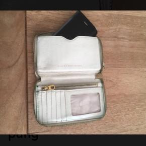 Varetype: Pung Clutch Størrelse: Lille Mellem 16 x 10 x 2.5 cm Farve: Råhvid  Lille, skøn pung fra Marc By Marc Jacobs. Lynlås rum med plads til mønter, sedler, kort mv. Flere små rum til kort.  Seperat rum med plads til f eks en I-Phone.   Også fin som lille Clutch.  Smuk patina.  Måler 16 x 10 x 2,5 cm