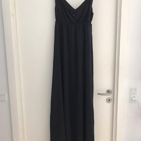 Lang kjole i tungt riflet stof - stoffet er lidt skinnende/blankt i overfladen.