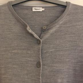Sød grå cardigan fra Filippa K i merino uld. Cardiganen passer formentlig også en xs, for er model short. Dvs den sidder pænt til og er ikke lang. Cardiganen er brugt, men i meget pæn stand.