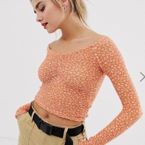 Sød top i orange med blomstret mønster i elastisk materiale. Kun brugt få gange. Størrelse small.