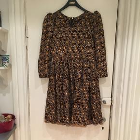 Flot hjemmesyet kjole i vintage / retro stil med pufærmer. Gul og mørkeblå. Materialet må være bomuld. Kjolen har lynlås i ryggen. Den mangler at blive lagt et par cm op for neden, men det kan man selv gøre, hvis man har en symaskine. Passer en str 38.