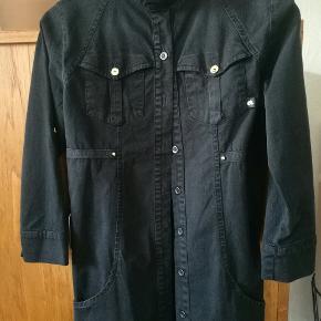 Fed kort skjortekjole i sort denim. Kan også anvendes som lang skjorte.  Den er figursyet.   Har 3/4 ærmer som kan smøges op.