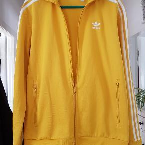 Klassisk Adidas Tracksuit jakke i sommergul. Brugt 1 gang og i perfekt stand. Bukser kan også findes på siden, men de er i str. M. Sættet var brugt 1 gang af min datter der er en klassisk str M (173cm, 58kg)