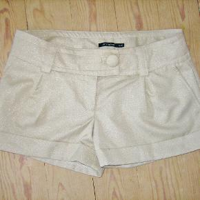 Super flotte sandfarvede shorts med en lille tynd sølvtråd indvævet i stoffet. Kun brugt 1 gang, så de er fuldstændig SOM NYE. Materialet er med elastan.  Livvidde: 44 cm x 2 Længde målt fra bæltestroppen og til nederste kant: 29 cm  Ingen byt og prisen er fast