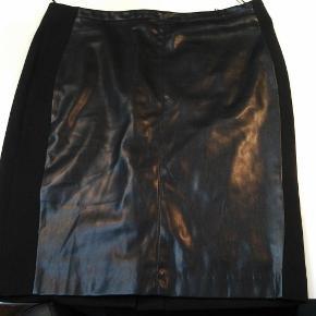 Varetype: Nederdel Farve: Sort  Sort nederdel fra esprit. Den er i stof og fake skind. Slids i bag. Den måler 45 cm i taljen og 56 i længde. Den har et tyndt glat lag stof på indersiden.