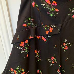 Smuk nederdel fra Heartmade i A-facon. Sort bundfarve med orange/lyserøde blomster. Lynlås i siden. Perfekt pasform. Kom med et bud