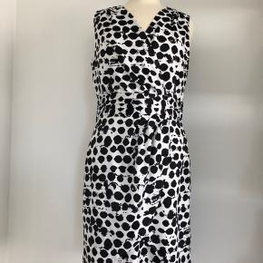 Sød kjole uden ærmer fra H&M i hvid med store, sorte abstrakte cirkler som motiv. Der er et fast lag-på-lag stykke i livet. Den krydser over øverst foran, og nederst krydser den også, men det er et pynte-kryds, da selve kjolen er nedenunder. Lukkes med lang lynlås på ryggen, som er neon-farvet men skjult. Fremstillet af blød polyester. Længde fra skulder er 92 cm, brystmålet er 86 cm, og taljen måler 78 cm. Bærer ikke præg af brug.