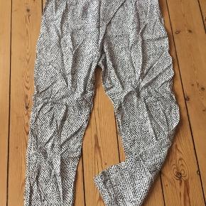 Løse bukser fra Vero Moda. Hvide med sorte prikker. Elastik i anklerne og bredt bånd om livet med lynlås i siden