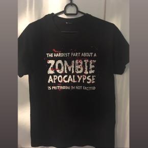 """Den absolut fedeste sorte t-shirt med print/merchandise t-shirt med zombie quote """"The hardest thing about a zombie apocalypse is pretending I'm not excited"""" (true though 😂), købt på nettet, størrelsen har jeg klippet ud men mener det er en str M/38, unisex design. 🧟♀️🧟♂️  Kan passes af flere forskellige størrelser, alt afhængig af hvordan  man gerne vil have den skal sidde.  Sælges da den desværre er for stor til mig.   Har kun brugt den få gange, derfor er standen næsten som ny, ingen slid og intet af printet/teksten er afskallet! 😊  Købt til omkring 200-250 kr.  Hvis den skal sendes, betaler køber fragt.  Mvh Betina Thy"""