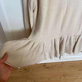 Super feminin strikket overdel med flæser i bunden.  Står i rigtig pæn stand og er kun brugt et par gange.  Meget elastisk i garnet