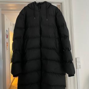 RAINS Long Puffer Jacket, str. M/L i sort sælges.  Den er købt midt december sidste år og er kun brugt et par uger. Der er ingen tydelige brugsspor og standen er derfor meget tæt på ny.