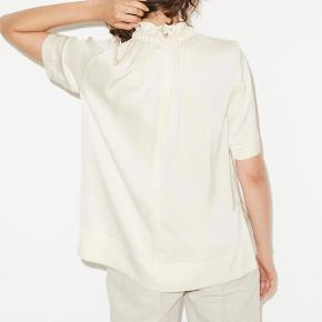 Victoriansk-inspireret høj hals og en let T-shirt-silhuet med et afslappet, men også meget elegant look. Med slidser i siderne og lidt længde bagpå er denne skjorte flatterende og chik, hvad enten du har den stoppet ned i eller ud over et par bukser. Almindelig pasform Lynlås i nakken 92 % silke, 8 % elastan