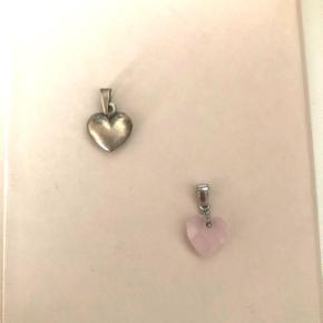 Sølv hjerte vedhæng og et lyserødt krystal hjerte vedhæng.