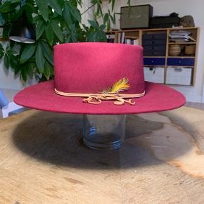 """Original Stetson hat fra slut 1960'erne eller de tidlige 70'ere.   Unik vinrød farve - meget sjælden.   Lige nu formet til """"Teardrop"""" men kan ved hjælp af et dampstrygejern formes til mange andre forme - f.eks. Den traditionelle """"Western"""" eller """"Porkpie"""".  4X Beaver kvalitet.  I ufatteligt god stand og taget godt vare på.   Skyggen er 9 cm / 3.5""""  Str. 7 1/8 eller 57 cm."""