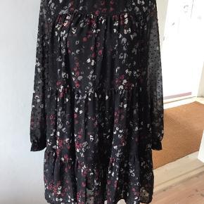 Sød let kjole med for i polyester. Lange ærmer med manchet. Farve sort med rød/råhvidt mønster.