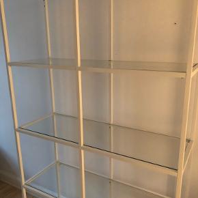 Reol fra Ikea med glashylder. Der er et lille mærke fra et klistermærke (billede 2), som formentligt kan fjernes. BYD.  Afhentes i Valby.
