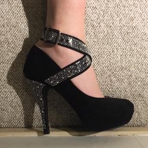 Helt ny, super flotte stiletter! Sort, ruskind look, sten på hæl og båndene der går omkring anklen. Str. 39, lidt små i størrelsen. Kun prøvet på, aldrig brugt da de er for små. Hælen er 12,5 cm. Pris: 150 kr. Åben for bud ved hurtig handel