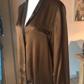 Super smuk pyjamas inspireret skjorte med sorte pipings. Farven er kobber. 100% viscose