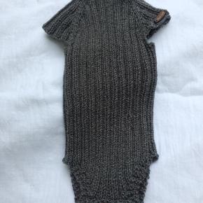 Babybody strikket i cottonwool (50% bomuld/50% uld) Str. 1-4 mdr. ca.  Den er meget elastisk,så det er svært at angive størrelse, og små børn er så forskellige. Den måler ca 35 cm i længden og brystvidden er alt mellem 32 og 52 cm, men selvfølgelig tager det af længden når den bliver trukket ud.