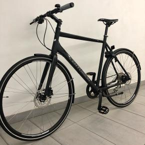 """Ny Centurion Basic Fitness Herre 8 Cykel sælges. Den har aldrig været brugt, da den er vundet i forbindelse med en konkurrence. Cyklen har 8 Altus udvendige gear og en værdi på 5499,-.  Derudover er den udstyret med ny lås fra Axa, ny støttefod og nye hjulskærme til en samlet værdi af 799,-.  Faktura medfølger på både cykel, lås, fod og skærme.  Farven er mat sort og størrelsen er 21,5"""".   Den er samlet og klargjort hos autoriseret cykelforhandler.  Samlet pris 5.000 kr.   Kontakt for yderligere information. For seriøse henvendelser er det muligt at komme forbi og se cyklen an."""