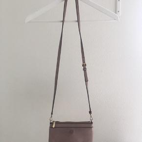 Fin lille taske som kan have mobil, pung osv  Der medfølger en lille 'pung' som sidder foran, hvori der er plads til kort og penge.