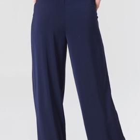Smukke bukser I dyb mørkeblå Sidder i taljen, med bred elastik i livet og lommer Aldrig brugt og med mærke i Model High Waist Pants