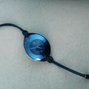 Dråbeformet Calvin Klein ur i blå nuancer med læderrem. Brugt få gange og virker upåklageligt. Skal have skiftet batteri. Købt i Paris.  Nypris: 1300,- Mp: 400,-