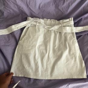 Hvid nederdel med bindebånd, købt i Barcelona. Føles som almindelig Bomuld,  og så har den lommer i siderne - ingenting bagpå.