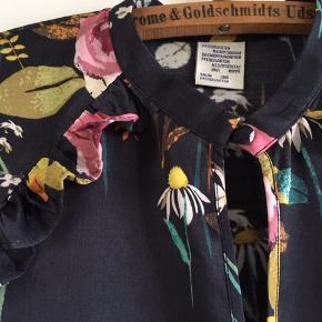 Smuk bluse med blomstermønster i 100% viskose. Rund hals med lille knap (også slids med lille knap på ærmerne). Flæsekant på forstykket - ryggen er helt glat. Kun brugt få gange og som ny. Længde ca. 62 cm, skulder ca. 38 cm og brystvidde ca. 96 cm.